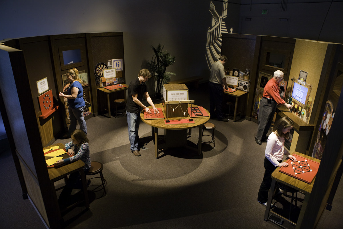 People interacting with Mindbender Mansion exhibit components