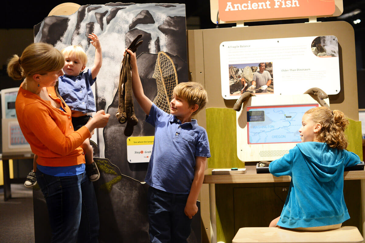 Visitors with 'Protecting an Ancient Fish' interactive