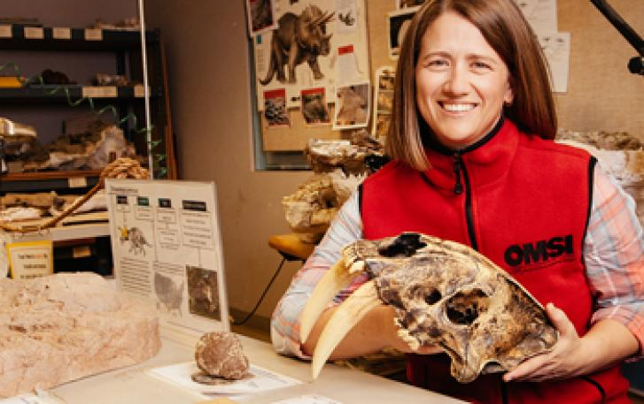 Volunteer shows off sabertooth skull in Paleontology Lab