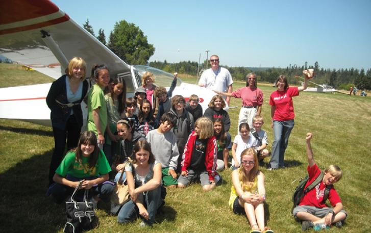 Student group poses with glider on airfield