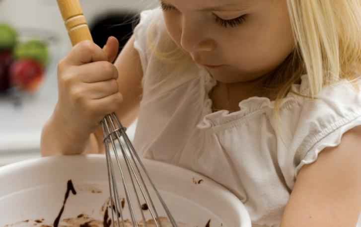 Young child with whisk and mixing bowl