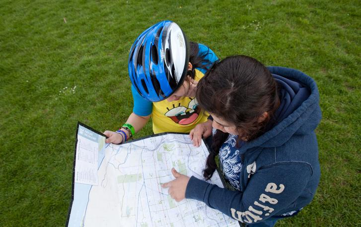 Pair of cyclists plotting bike route on map