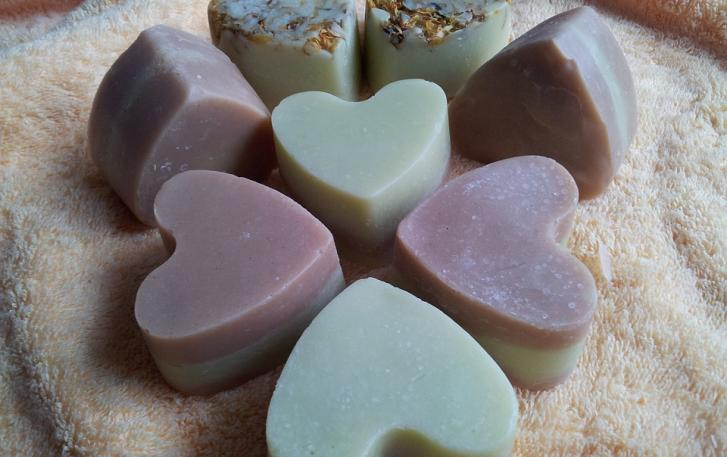 purple and blue heart shaped soap sitting on a towel