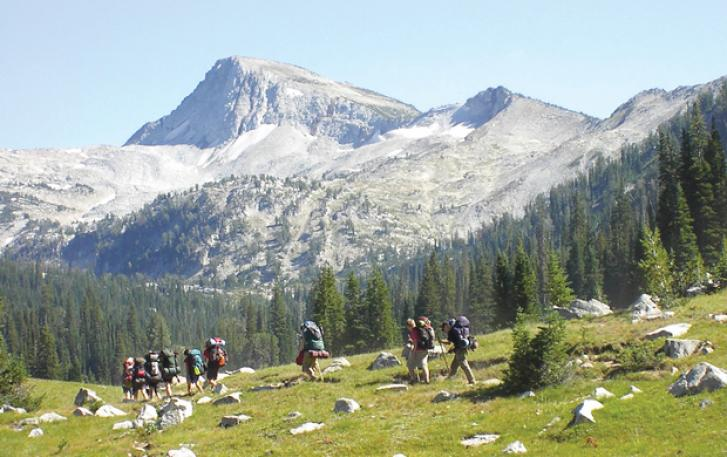 Backpackers crossing field in Wallowa Mountains