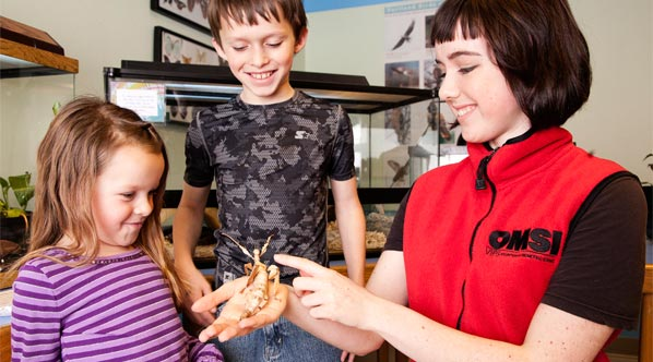 OMSI volunteer showing an insect to two children